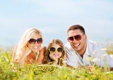 Famille heureuse avec le ciel bleu et l'herbe verte Image libre de droits