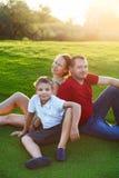 Famille heureuse avec le fils s'asseyant sur l'herbe en parc Photos stock