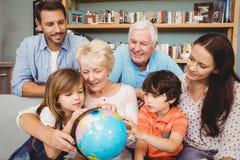 Famille heureuse avec le globe tout en se reposant sur le sofa Images libres de droits
