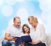 Famille heureuse avec le livre à la maison Photo stock