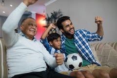 Famille heureuse avec le match de football de observation augmenté par bras Image stock