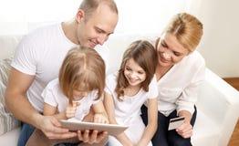 Famille heureuse avec le PC de comprimé et la carte de crédit Image stock