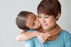 Famille heureuse avec le sourire, fille positive embrassant son mother Photographie stock libre de droits