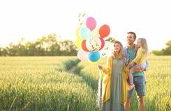 Famille heureuse avec les ballons colorés dans le domaine images stock