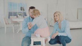 Famille heureuse avec leur beau bébé près de la chaise Mouvement lent banque de vidéos