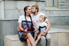 Famille heureuse avec un petits beaux bébé, mère et fille dans des robes avec la sucrerie Image stock