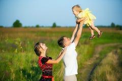 Famille heureuse ayant l'amusement dehors dans le pré d'été images libres de droits