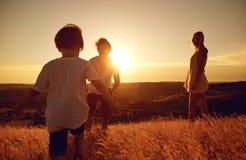 Famille heureuse ayant l'amusement jouant au coucher du soleil sur la nature photographie stock