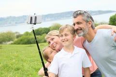 Famille heureuse ayant l'amusement prenant le selfie dehors Photographie stock libre de droits