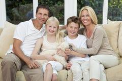 Famille heureuse ayant l'amusement se reposer avec le crabot d'animal familier Image stock