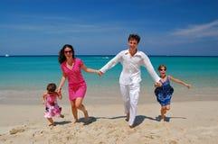 Famille heureuse ayant l'amusement sur la plage Photographie stock libre de droits