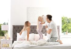 Famille heureuse ayant le combat d'oreiller sur le lit photographie stock