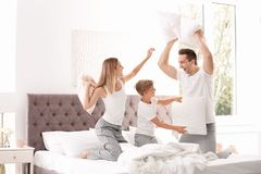 Famille heureuse ayant le combat d'oreiller sur le lit images stock