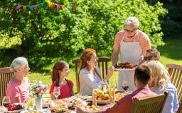 Famille heureuse ayant le dîner ou la réception en plein air d'été Photos stock