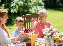 Famille heureuse ayant le dîner ou la réception en plein air d'été photographie stock libre de droits