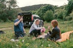 Famille heureuse ayant le thé de déjeuner et de boissons camping, week-end, pique-nique homme, femme, fille, croisement, voiture  photographie stock