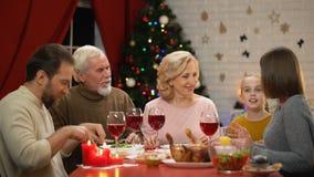 Famille heureuse ayant les lumières saines savoureuses de dîner de Noël ensemble sur l'arbre scintillant banque de vidéos