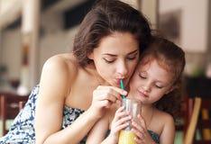 Famille heureuse buvant du jus d'orange et joying ensemble en café Image stock