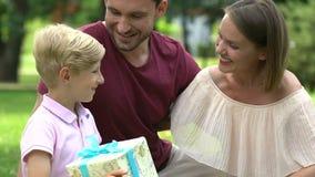 Famille heureuse célébrant l'anniversaire de fils, présentant le cadeau gentil, parents affectueux banque de vidéos
