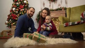 Famille heureuse célébrant la mère de Noël ensemble, le père et le petit bébé s'asseyant sur le plancher dans la chambre avec clips vidéos
