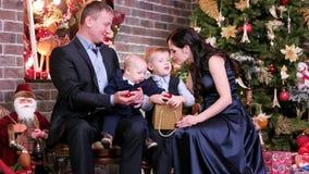 Famille heureuse célébrant le ` s Ève de nouvelle année, mère et père écoutant un vers qui indique le fils le plus âgé clips vidéos