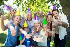 Famille heureuse célébrant un anniversaire avec des pouces  Photographie stock