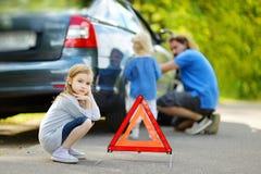 Famille heureuse changeant une roue de voiture Photographie stock libre de droits