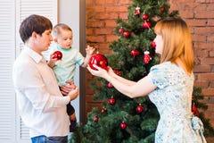 Famille heureuse décorant un arbre de Noël avec des babioles dans le salon Image stock
