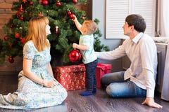 Famille heureuse décorant un arbre de Noël avec des babioles dans le salon Photographie stock