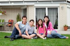 Famille heureuse détendant dans l'arrière-cour de la maison neuve Images libres de droits