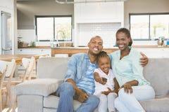 Famille heureuse détendant sur le divan images libres de droits