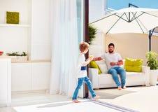 Famille heureuse détendant sur le patio de dessus de toit avec la cuisine de l'espace ouvert au jour d'été chaud image stock