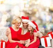 Famille heureuse dans des chapeaux d'aide de Santa avec des boîte-cadeau Image stock