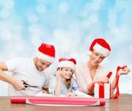 Famille heureuse dans des chapeaux d'aide de Santa emballant le cadeau Photographie stock libre de droits