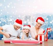 Famille heureuse dans des chapeaux d'aide de Santa emballant le cadeau Photos stock