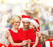 Famille heureuse dans des chapeaux de Santa avec la carte de voeux Photo libre de droits