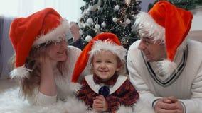 Famille heureuse dans des chapeaux du ` s de Santa se trouvant sur le tapis banque de vidéos