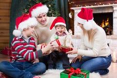 Famille heureuse dans des chapeaux rouges avec des cadeaux photographie stock libre de droits
