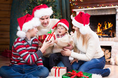 Famille heureuse dans des chapeaux rouges avec des cadeaux se reposant à photo libre de droits