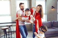 Famille heureuse dans des costumes de super héros jouant ensemble image libre de droits