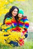 Famille heureuse dans des hoodies d'arc-en-ciel Photographie stock libre de droits