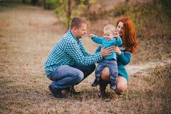 Famille heureuse dans des vêtements élégants bleus marchant dans la forêt d'automne Photographie stock