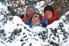 Famille heureuse dans l'arbre de sapin de neige images stock