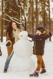 Famille heureuse dans l'habillement chaud Mère et fils de sourire rendant un bonhomme de neige extérieur Le concept des activités Image libre de droits