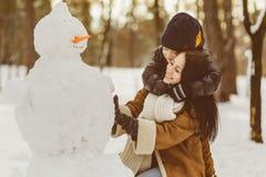 Famille heureuse dans l'habillement chaud Mère et fils de sourire rendant un bonhomme de neige extérieur Le concept des activités Images libres de droits