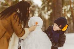 Famille heureuse dans l'habillement chaud Mère et fils de sourire rendant un bonhomme de neige extérieur Le concept des activités Image stock