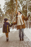 Famille heureuse dans l'habillement d'hiver La mère et le fils de sourire marchent au parc Photos libres de droits