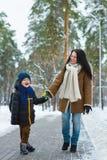 Famille heureuse dans l'habillement d'hiver La mère et le fils de sourire marchent au parc Image libre de droits