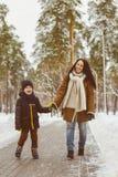 Famille heureuse dans l'habillement d'hiver La mère et le fils de sourire marchent au parc Photos stock