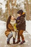 Famille heureuse dans l'habillement d'hiver Mère et fils de sourire extérieurs Photo stock